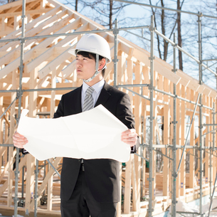 建設途中の家の前で図面を持ち真剣な表情をするビジネスマンの写真素材 [FYI01954052]
