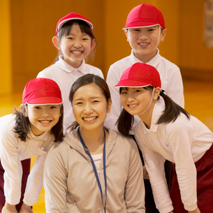 体育館で微笑む先生と小学生の写真素材 [FYI01954070]