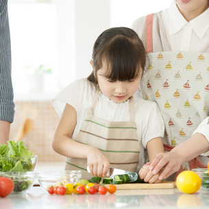 キッチンで野菜を切る女の子の写真素材 [FYI01954080]