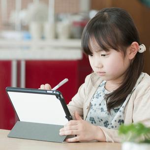 タブレットPCを操作する女の子の写真素材 [FYI01954088]