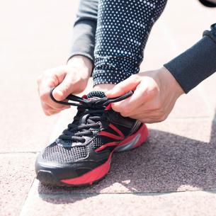 靴紐を結び直す女性の足元の写真素材 [FYI01954110]