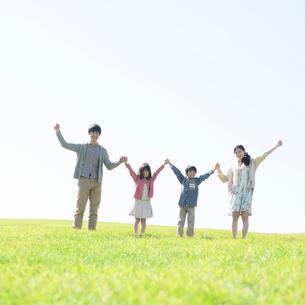 草原で手をつなぐ家族の写真素材 [FYI01954146]