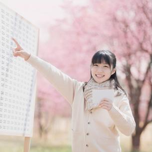 合格発表のボードを見て喜ぶ女子中学生の写真素材 [FYI01954157]