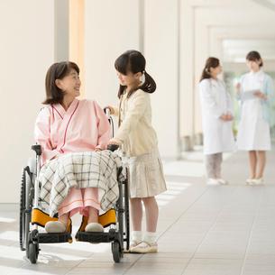 車椅子に乗る祖母と話をする女の子の写真素材 [FYI01954164]