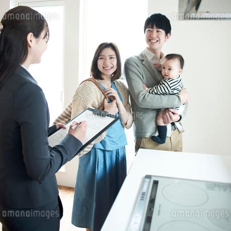 部屋の内見をする家族とビジネスウーマンの写真素材 [FYI01954177]
