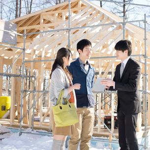 建設途中の家の前でビジネスマンと話をする夫婦の写真素材 [FYI01954189]