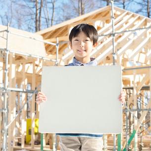 建設途中の家の前でメッセージボードを持ち微笑む男の子の写真素材 [FYI01954196]