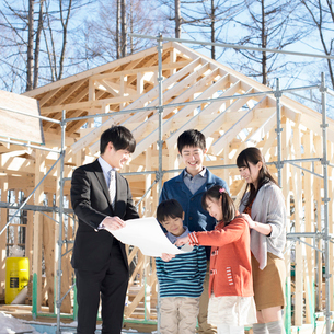 建設途中の家の前でビジネスマンと話をする家族の写真素材 [FYI01954206]