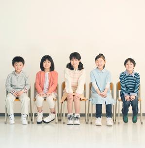 教室で椅子に座り微笑む小学生の写真素材 [FYI01954244]