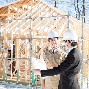建設途中の家の前で打ち合わせをするビジネスマンと作業員の写真素材 [FYI01954267]