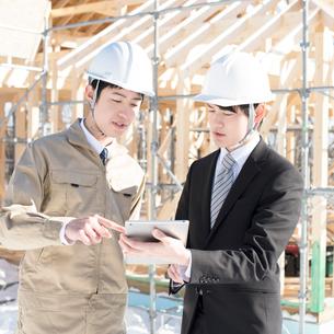 建設途中の家の前でビジネスマンと打ち合わせをする作業員の写真素材 [FYI01954276]