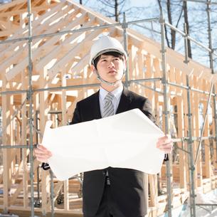 建設途中の家の前で図面を持ち真剣な表情をするビジネスマンの写真素材 [FYI01954279]