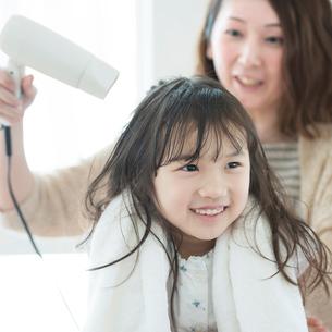 母親に髪を乾かしてもらう女の子の写真素材 [FYI01954308]