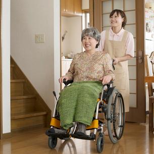 シニア女性の乗る車椅子を押すホームヘルパーの写真素材 [FYI01954311]