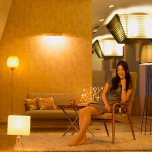 椅子に座り微笑む女性の写真素材 [FYI01954339]