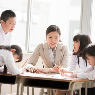 グループ学習をする小学生と先生の写真素材 [FYI01954345]