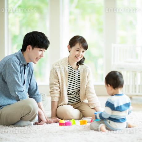 子供とおもちゃで遊ぶ両親の写真素材 [FYI01954363]