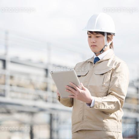 工事現場でタブレットPCを操作する作業員の写真素材 [FYI01954388]