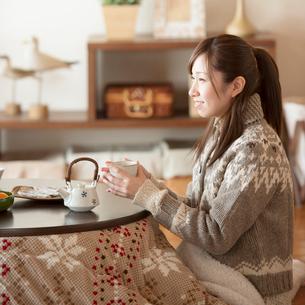 こたつでお茶を飲み微笑む女性の写真素材 [FYI01954406]