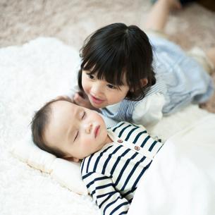 寝ている赤ちゃんに寄り添う女の子の写真素材 [FYI01954412]