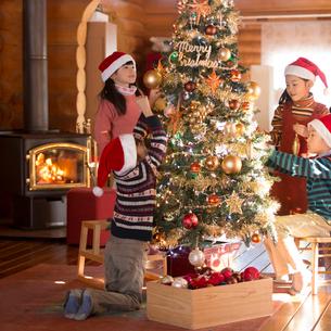 クリスマスツリーに飾り付けをする子供達の写真素材 [FYI01954490]
