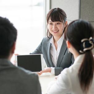 タブレットPCを持ち説明をするビジネスウーマンの写真素材 [FYI01954500]