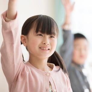 教室で手を挙げる小学生の写真素材 [FYI01954577]