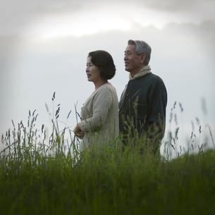 草原に立つシニア夫婦の写真素材 [FYI01954619]