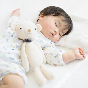 お昼寝をする赤ちゃんとクマのぬいぐるみの写真素材 [FYI01954623]
