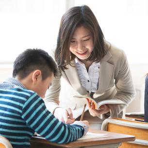 教室で先生に勉強を教わる小学生の写真素材 [FYI01954643]
