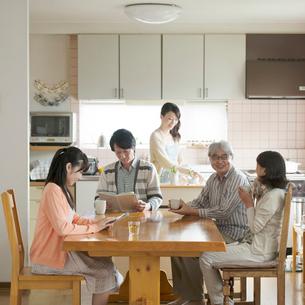 リビングで談笑をする3世代家族の写真素材 [FYI01954653]