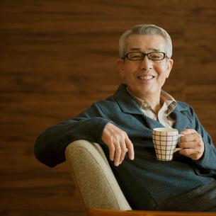 コーヒーカップを持ち微笑むシニア男性の写真素材 [FYI01954717]