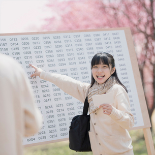 合格発表のボードを見て喜ぶ女子中学生の写真素材 [FYI01954762]