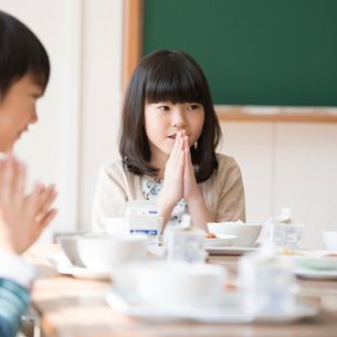 給食を前に手を合わせる小学生の写真素材 [FYI01954764]