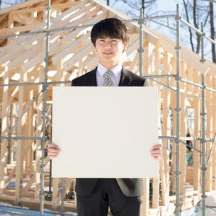 建設途中の家の前でメッセージボードを持ち微笑むビジネスマンの写真素材 [FYI01954769]
