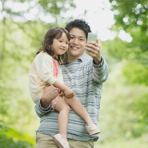 新緑の中でスマートフォンの画面を見る親子の写真素材 [FYI01954771]