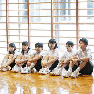 体育館で体育座りをする学生の写真素材 [FYI01954773]