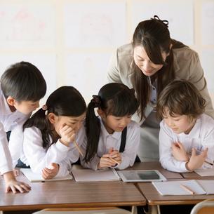 タブレットPCを見る小学生と先生の写真素材 [FYI01954781]