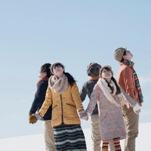 雪原で手をつなぎ空を見上げる若者たちの写真素材 [FYI01954854]
