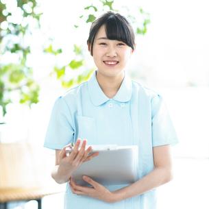 カルテを持ち微笑む看護師の写真素材 [FYI01954974]