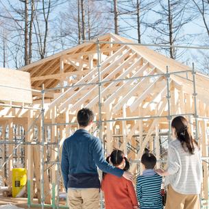 建設途中の家を眺める家族の後姿の写真素材 [FYI01954993]