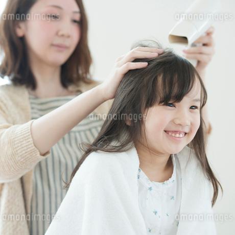 母親に髪を乾かしてもらう女の子の写真素材 [FYI01955046]