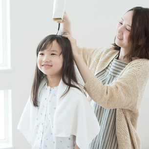 母親に髪を乾かしてもらう女の子の写真素材 [FYI01955059]