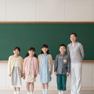 黒板の前で微笑む小学生と先生の写真素材 [FYI01955064]