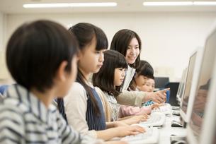 パソコンの授業を受ける小学生と先生の写真素材 [FYI01955119]