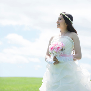 草原でブーケを持ち微笑む花嫁の写真素材 [FYI01955150]