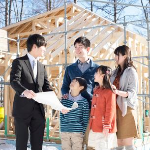 建設途中の家の前でビジネスマンと話をする家族の写真素材 [FYI01955155]