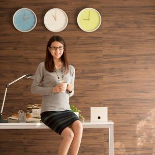 コーヒーカップを持ち机に寄りかかるビジネスウーマンの写真素材 [FYI01955161]