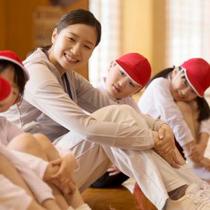 体育館で体育座りをする先生と小学生の写真素材 [FYI01955205]