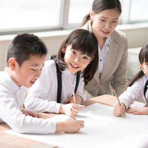 グループ学習をする小学生と先生の写真素材 [FYI01955206]